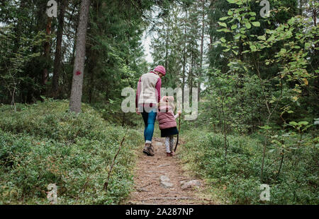 mother holding her daughters hand walking through the forest in fall - Stock Photo