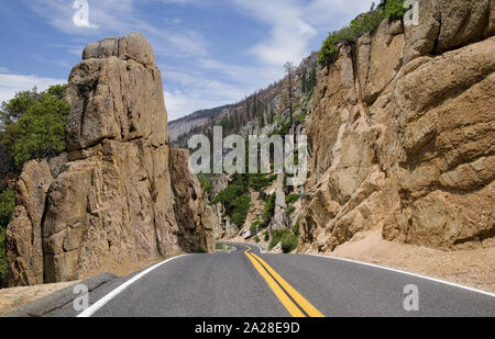 California Scenic Mountain Road:  A two lane highway passes through a cut between large rocks as it crosses the Sierra Nevada Mountains. - Stock Photo
