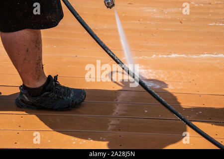 Legs of a man wearing black shorts washing the dirt off of a brown wooden deck with a wide spray of water from a metal nozzle. The man is wearing blac - Stock Photo
