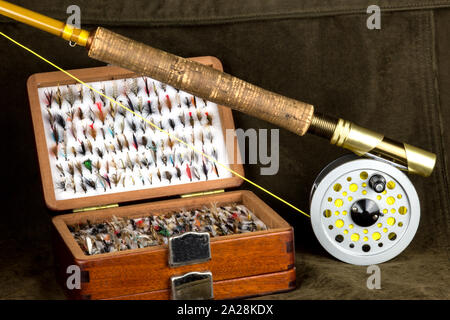 Fly fishing rod and old fly box on outdoor coat - Stock Photo