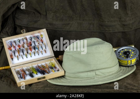 Trout fly fishing rod with fly box and hat on an outdoor coat - Stock Photo