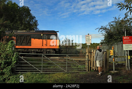 A orange diesel locomotive crosses Mares Close level crossing as a walker waits for it to pass on the railway branch line to Lynemouth power station. - Stock Photo