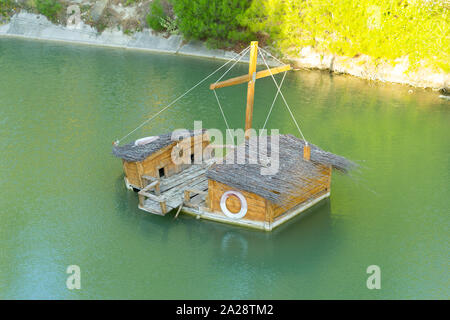 Duck house made from wooden boat, floats in the emerald water of a small pond. Sunny day. People caring for the birds. - Stock Photo