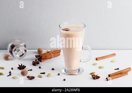 Masala chai or  spiced tea  in glass cup with fresh ginger, cardamom, cinnamon, cloves and star anise that bring you comfort and warmth . Top view. - Stock Photo