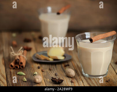 Masala tea in a glass.Traditional indian drink masala chai tea with milk and spices cinnamon stick, green cardamom, anise star, ginger.Selective focus. - Stock Photo