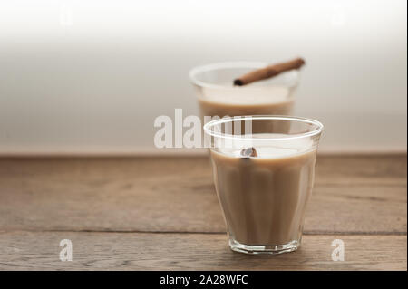 Indian masala tea with cinnamon sticks in two glasses on wooden background. Selective focus. Natural light. Horizontal with copy space. - Stock Photo
