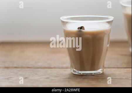 Spicy masala chai with milk in a glass  and a cinnamon stick over it in wooden background.Selective focus.Image with copy space,horizontal. - Stock Photo