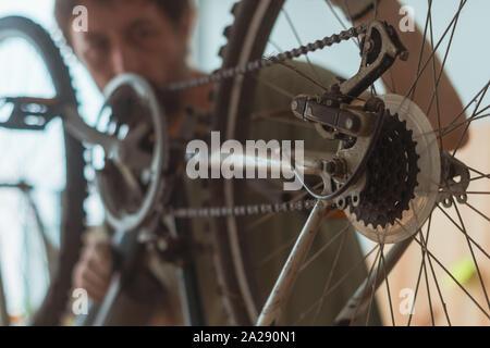 Bicycle mechanic repairing old mountain bike in workshop, selective focus