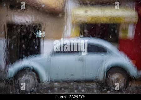 Classic Volkswagen Beetle in a raining day in a village street - Stock Photo