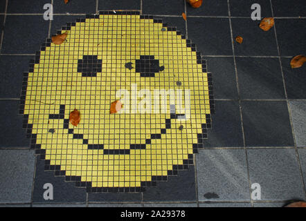 Kuala Lumpur, Malaysia - mosaic of an smiling face emoticon on a gray tiles sidewalk, and some fallen tree leaves. - Stock Photo