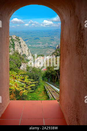 Picturesque view through window on famous monastery Santa Maria de Montserrat located in mountains. Catalonia, Spain - Stock Photo