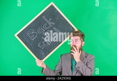 Keep working. Teacher with tousled hair stressful about school year beginning. Teaching stressful occupation. Teacher bearded man holds blackboard with inscription back to school green background. - Stock Photo