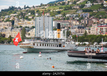 The most beautiful  steam boat called La Suisse with Swiss flag waving at the stern approaching Montreux pier on Swiss Riviera, Vaud, Switzerland - Stock Photo