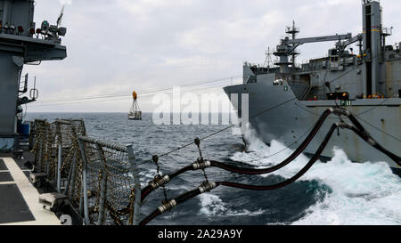 190926-N-PC620-0072  ARCTIC OCEAN (Sept. 26, 2019) The dry cargo and ammunition ship USNS William McLean (T-AKE 12), right, sends fuel and supplies to the Ticonderoga-class guided-missile cruiser USS Normandy (CG 60) during a replenishment-at-sea Sept. 26, 2019. Normandy is operating in the Atlantic in support of naval operations to maintain maritime stability and security in order to ensure access, deter aggression and defend U.S., allied and partner interests. (U.S. Navy photo by Mass Communication Specialist 2nd Class Michael H. Lehman/Released) - Stock Photo
