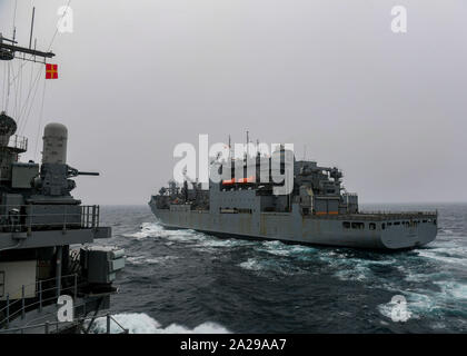 190926-N-PC620-0013  ARCTIC OCEAN (Sept. 26, 2019) The Ticonderoga-class guided-missile cruiser USS Normandy (CG 60), left, makes its approach to the dry cargo and ammunition ship USNS William McLean (T-AKE 12) during a replenishment-at-sea Sept. 26, 2019. Normandy is operating in the Atlantic in support of naval operations to maintain maritime stability and security in order to ensure access, deter aggression and defend U.S., allied and partner interests. (U.S. Navy photo by Mass Communication Specialist 2nd Class Michael H. Lehman/Released) - Stock Photo