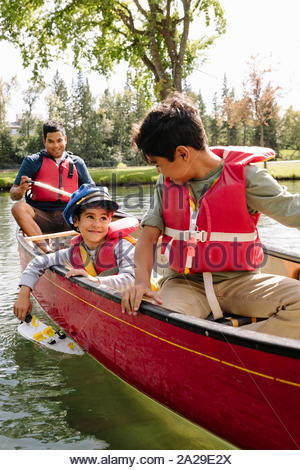 Young boy playing with toy boat in canoe with brother and father - Stock Photo