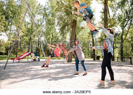 Children being pushed by mothers on swings in park - Stock Photo