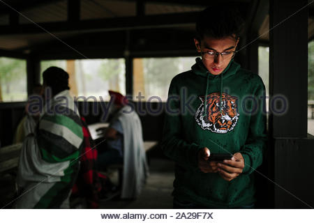 Portrait of Indian teenager using smartphone in log cabin - Stock Photo
