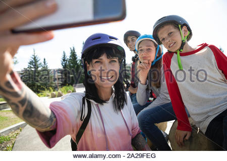 Family taking selfie with camera phone in sunny skate park - Stock Photo