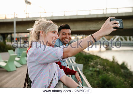 Happy young couple taking selfie with camera phone on urban boardwalk - Stock Photo