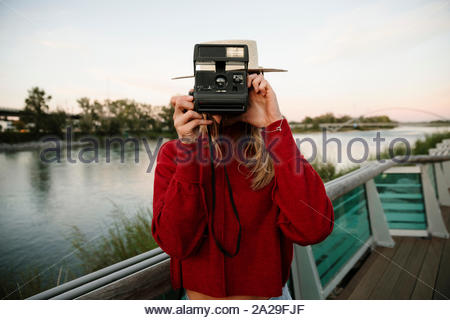 Portrait young woman using instant camera at waterfront - Stock Photo