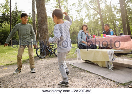 Parents sitting on picnic bench watching boys playing in park - Stock Photo