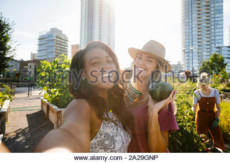 Personal perspective young women friends taking selfie in sunny, urban community garden - Stock Photo