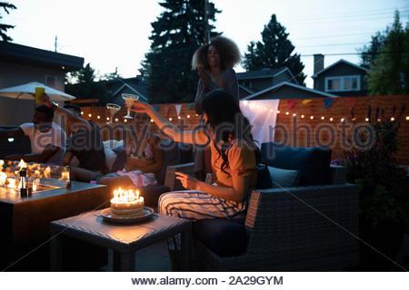 Friends celebrating birthday on summer patio at night - Stock Photo