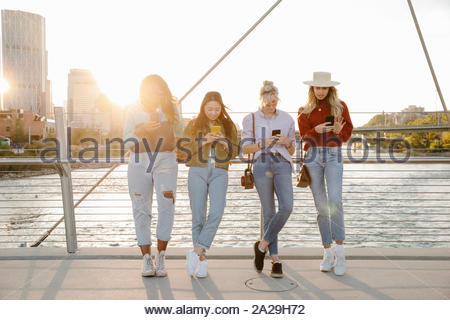 Young women friends using smart phones on sunny, urban bridge - Stock Photo