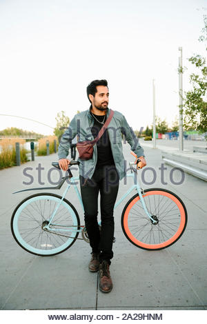 Portrait confident, cool young man with bicycle - Stock Photo