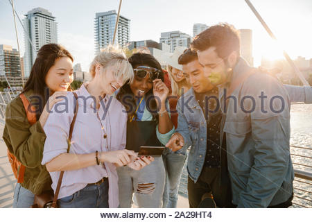 Happy young adult friends using digital tablet on sunny, urban bridge - Stock Photo