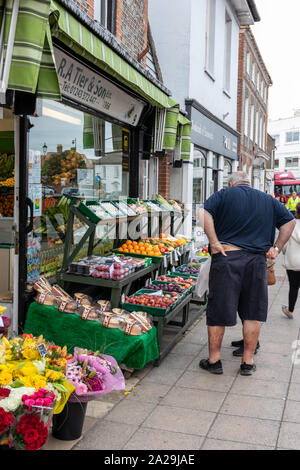 People looking at fruit and vegetables on the stand of a tradition greengrocers in an English village - Stock Photo