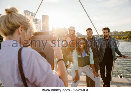 Young woman with digital tablet camera photographing friends on sunny, urban bridge - Stock Photo