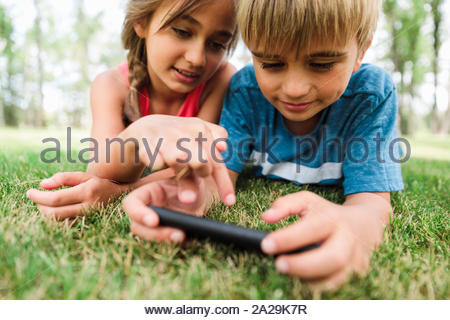 Boy and girl lying on grass using smartphone - Stock Photo