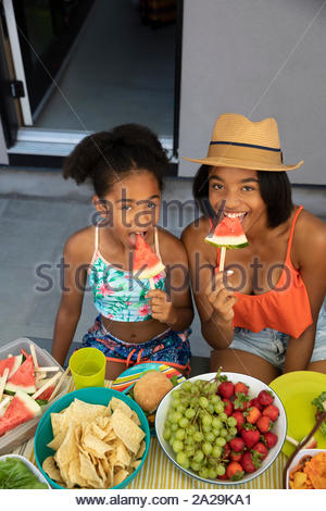 Portrait smiling, confident sisters eating watermelon slices on summer patio - Stock Photo