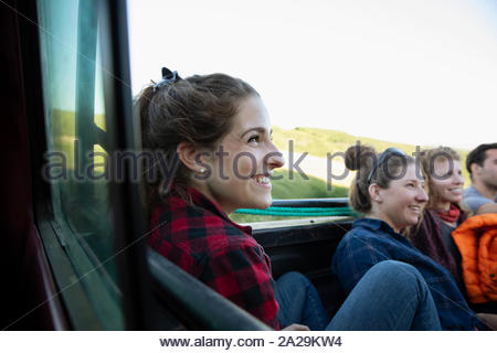 Friends traveling in back of pickup truck - Stock Photo