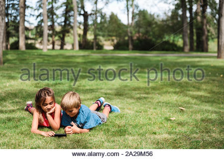 Boy and girl lying on grass using smartphone in park - Stock Photo