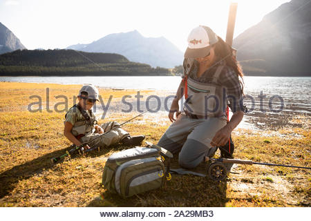 Mother and son fly fishing at sunny lakeside - Stock Photo