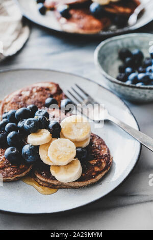Healthy comfort breakfast set. Flat-lay of banana pancakes with fresh blueberry and honey in plates over white marble table background - Stock Photo