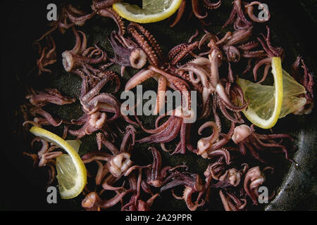 Grilled squids calamari tentacles with lemon in cast iron pan. Close up, food background, top view - Stock Photo