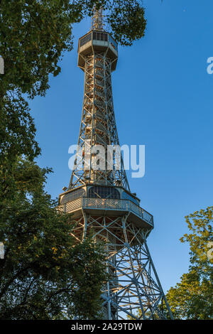 Old Petrin radio tower made of steel in Prague on the Petrin hill in the district of Lesser Town with viewing platform in summer with blue sky and tre - Stock Photo