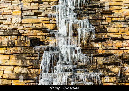 Icicles Dripping down the side of a Rock Wall - Stock Photo