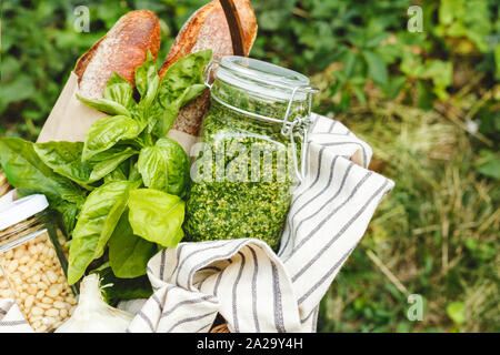 Picnic basket with homemade pesto sauce in a glass jar with ingredients basil, pine nuts and baguette outdoors. Pesto - traditional italian sauce for - Stock Photo