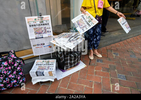 October 2 2019.  Hong Kong resumes business the morning after violent protests on October 1 2019. A woman sells newspapers headlining the National Day protests. - Stock Photo