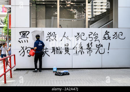 October 2 2019.  Hong Kong resumes business the morning after violent protests on October 1 2019. Workers clean graffiti off of walls and billboards. - Stock Photo