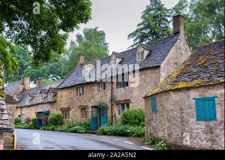Typical pretty cottages with climbing plants with yellow Cotswold limestone walls and slate roof with garden of roses in Snowshill, Cotswolds England - Stock Photo
