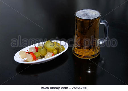 Banderillas a Classic Spanish tapa make with gherkin pickled, pearl onions, green olives and red peppers, with a beer mug, on a black table - Stock Photo