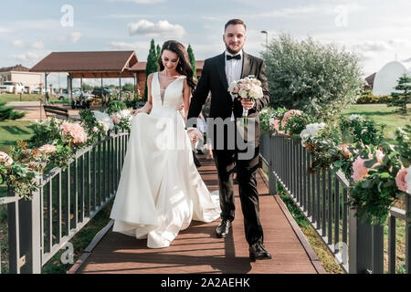 bride and groom walking on a narrow bridge. holidays and traditions - Stock Photo