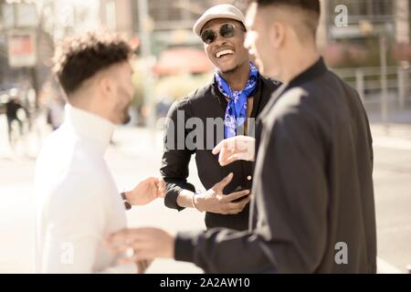 three male friends discussing on street in city Frankfurt, Germany