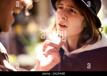 defiant woman with raised chin looking at laughing counterpart at night, nightlife in city Berlin, Germany - Stock Photo